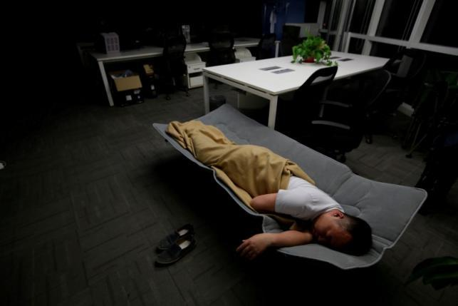Ma Zhenguo, a system engineer at RenRen Credit Management Co., sleeps on a camp bed at the office after finishing work early morning, in Beijing, China, April 27, 2016.  REUTERS/Jason Lee