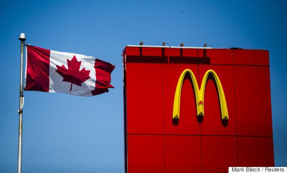A Canadian flag waves beside McDonalds fast food restaurant in Toronto, May 1, 2014.  About 400,000 people came to Canada under the government's temporary foreign worker program, which is designed to fill jobs for which there are no qualified Canadian candidates. The program has been hugely popular with employers, ballooning from 100,000 workers in 2002. But the backlash against it has also grown as the program, initially designed to help the booming resource industry, has expanded to lower-skilled jobs, especially at restaurant chains such as McDonald's Corp and Tim Hortons Inc. To match Feature CANADA-EMPLOYMENT/TEMPORARY   REUTERS/Mark Blinch (CANADA - Tags: BUSINESS EMPLOYMENT FOOD POLITICS)