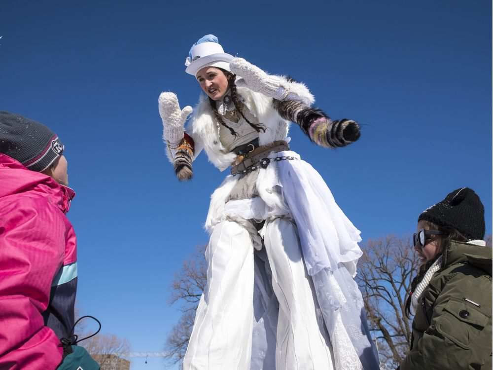 A stilt walker entertains children during the opening day of the 2017 Winterlude Festival at Jacques Cartier Park in Gatineau, Friday, February 3, 2017.