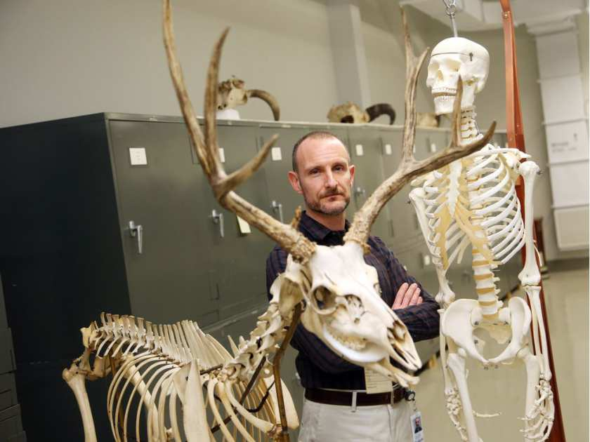 dr-scott-rufolo-stands-between-a-human-skeleton-reproduction1