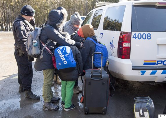 A family of asylum claimants huddle as they are arrested after crossing the border into Canada from the United States, Monday, February 20, 2017 near Hemmingford, Que. A growing number of people have been walking across the border into Canada to claim refugee status. THE CANADIAN PRESS/Paul Chiasson