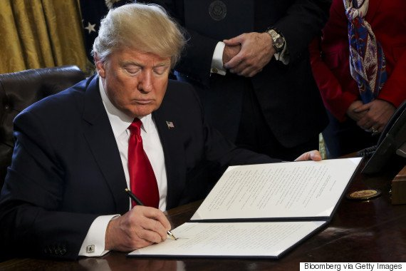 U.S. President Donald Trump signs an Executive Order related to the review of the Dodd-Frank Act in the Oval Office of the White House, in Washington, D.C., U.S., on Friday, Feb. 3, 2017. Trump will order a sweeping review of the Dodd-Frank Act rules enacted in response to the 2008 financial crisis, a White House official said, signing an executive action Friday designed to significantly scale back the regulatory system put in place in 2010. Photographer: Aude Guerrucci/Pool via Bloomberg