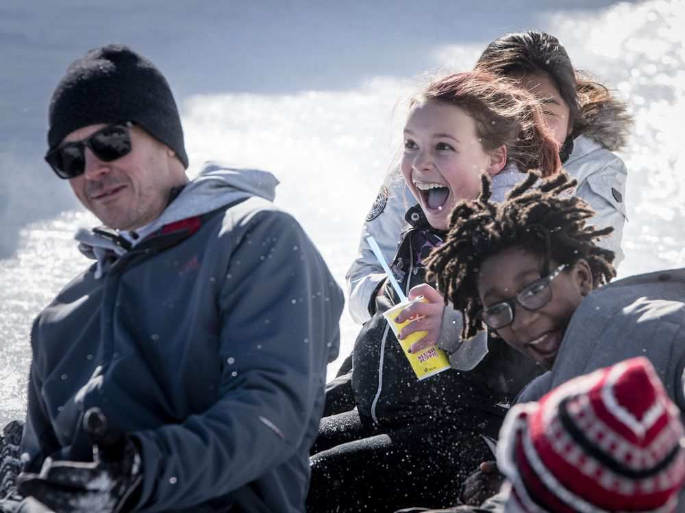 Serena Lake, center, screams at she descends an ice slide with friends from Pierre Elliot Trudeau school during the opening day of the 2017 Winterlude Festival at Jacques Cartier Park in Gatineau, Friday, February 3, 2017.