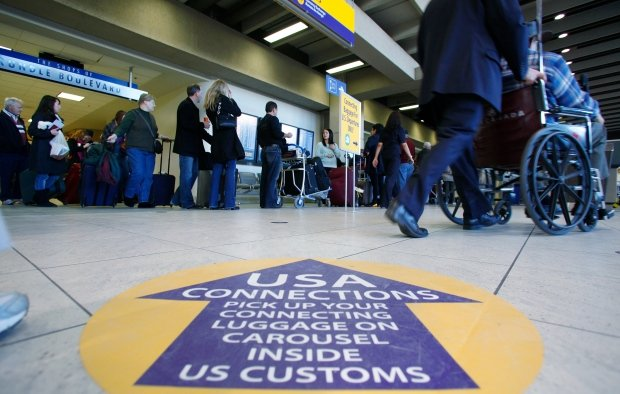 Passengers wait to check in and go through U.S. Customs at Calgary International Airport. (Todd Korol/Reuters)